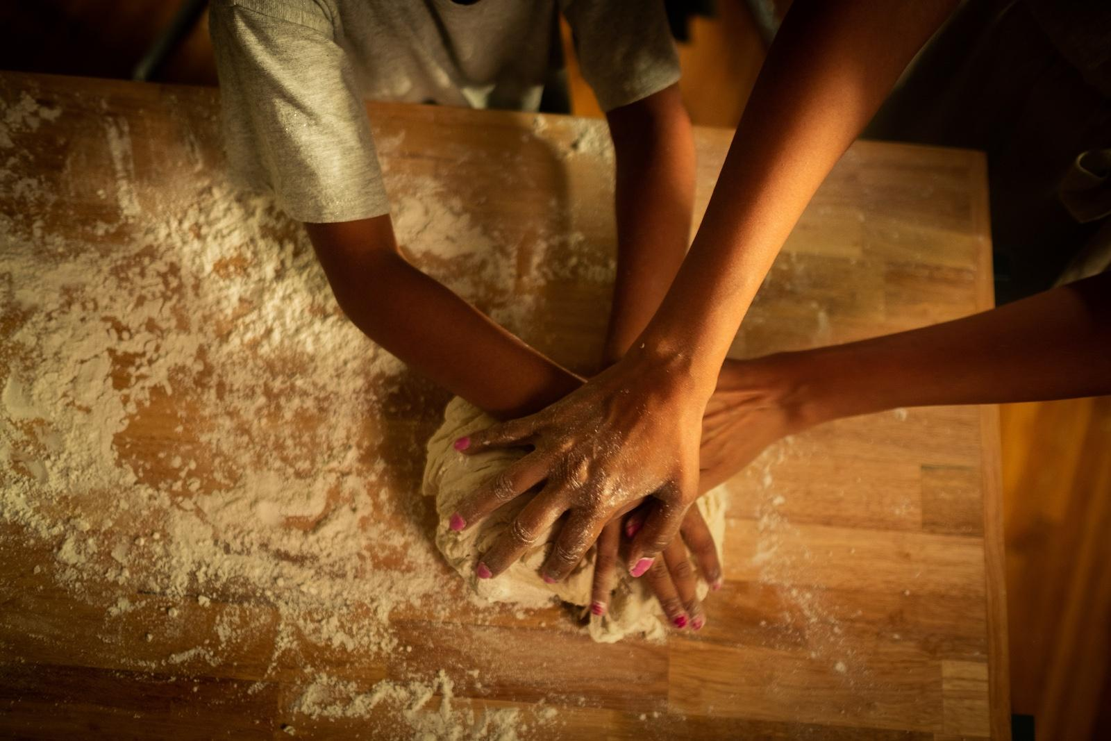 Parent and child knead bread dough