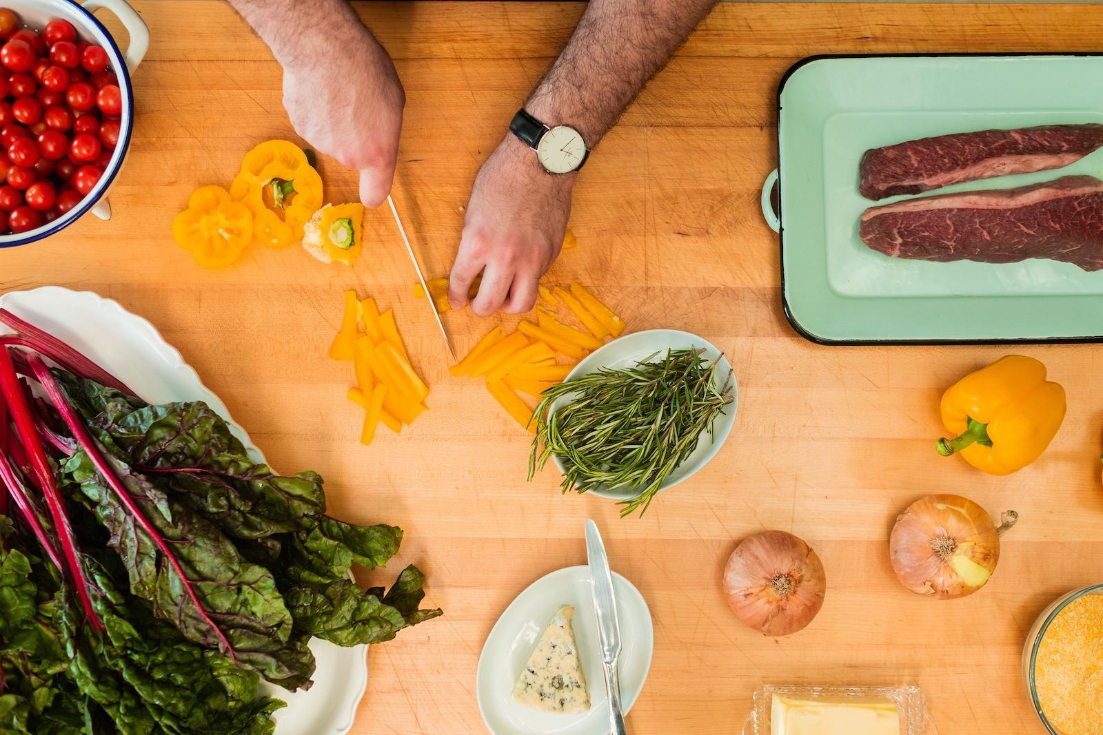 Man chops carrots on kitchen countertop