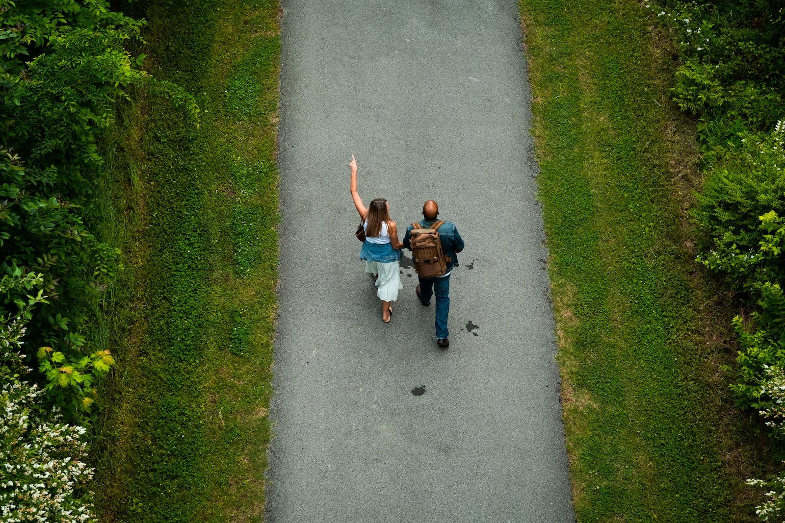 Two people go for walk along a path