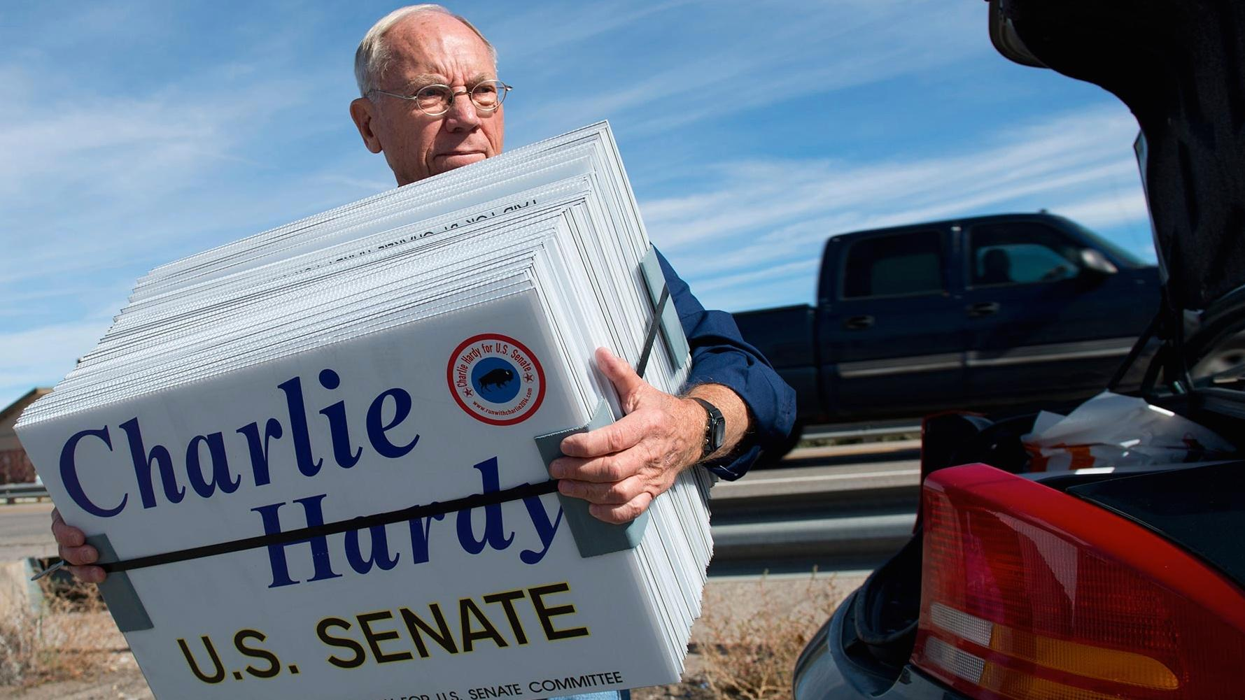 Charlie Hardy for U.S. Senate, holding a stack of yard signs.
