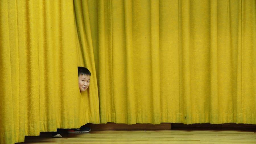 A boy peeking through stage curtains.