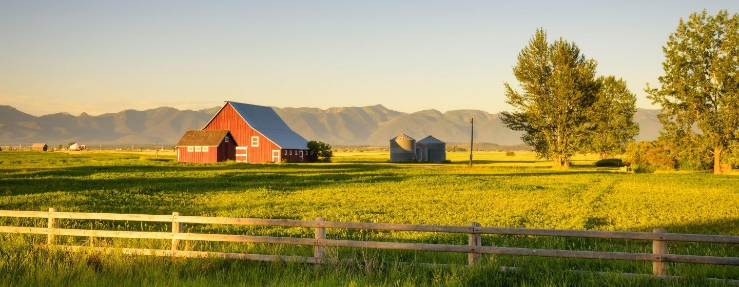 Summer sunset with a red barn and mountains in rural Montana