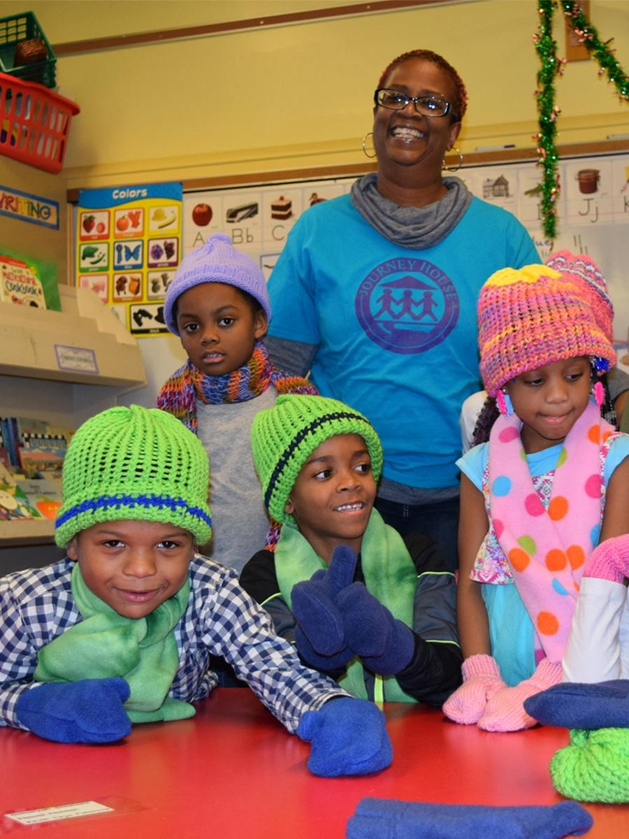 Photograph of children receiving knit hats and mittens