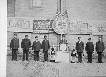 Photo of Men in Line with Large Bottles and Logo at Pabst Brewing Co