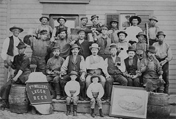 Photo of Fred Miller with Brewery Workers and Beer Mugs
