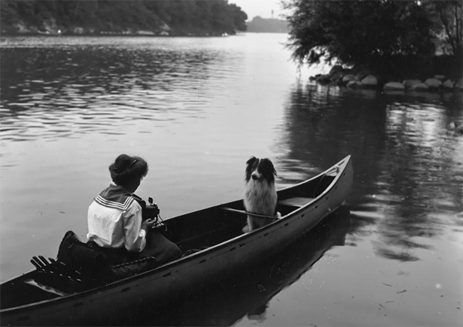 Photo of Woman Taking Photograph of Dog While Both in a Canoe