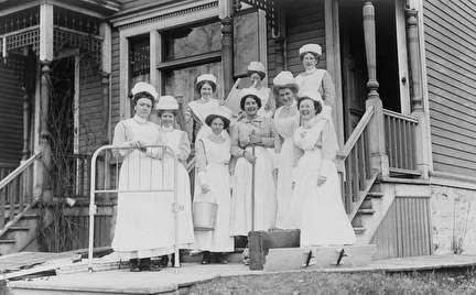Photo of Group of Nurses Standing Outside the Front of a House