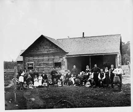 Photo of Large Group Shot in front of Early House, 1800s