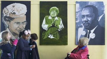Eva Kor in front of a stylized portrait painting of her with children in the right hand side of the photo