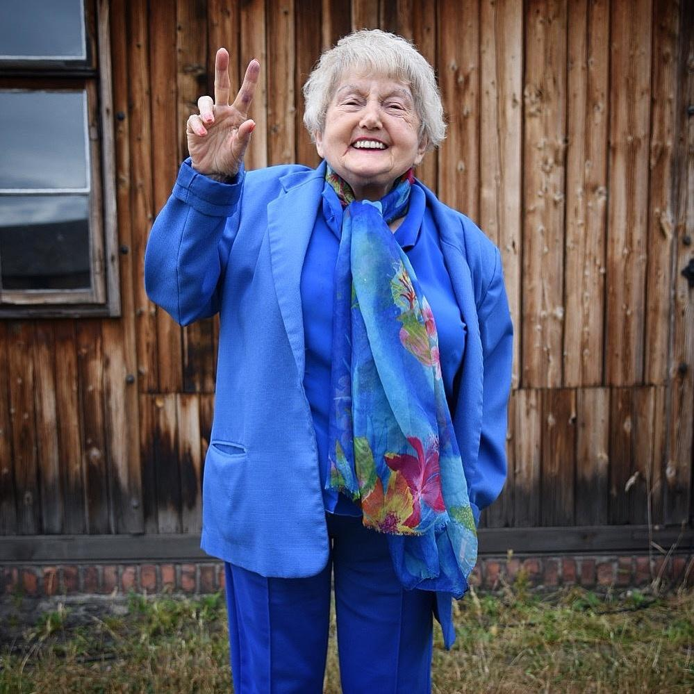 Eva Kor smiles while making a peace symbol with her hand.