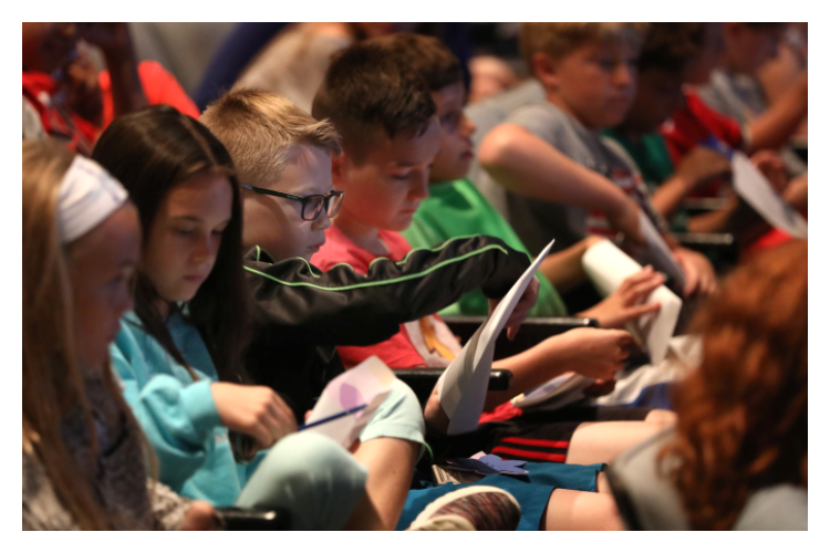 """Students writing down one thing they can do to make the world better following a screening of """"Eva: A-7063"""" at Newfields in Indianapolis."""