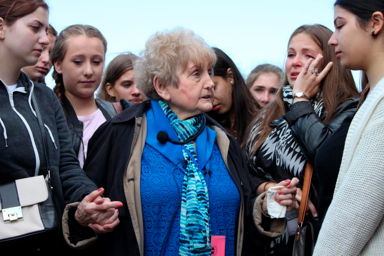Eva Kor talks to an emotional group of girls from Germany at Auschwitz.
