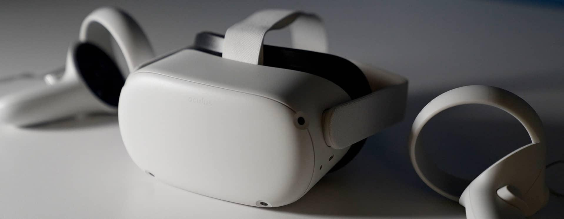 White Oculus brand VR head set on white table top with hand controllers and dramatic lighting.