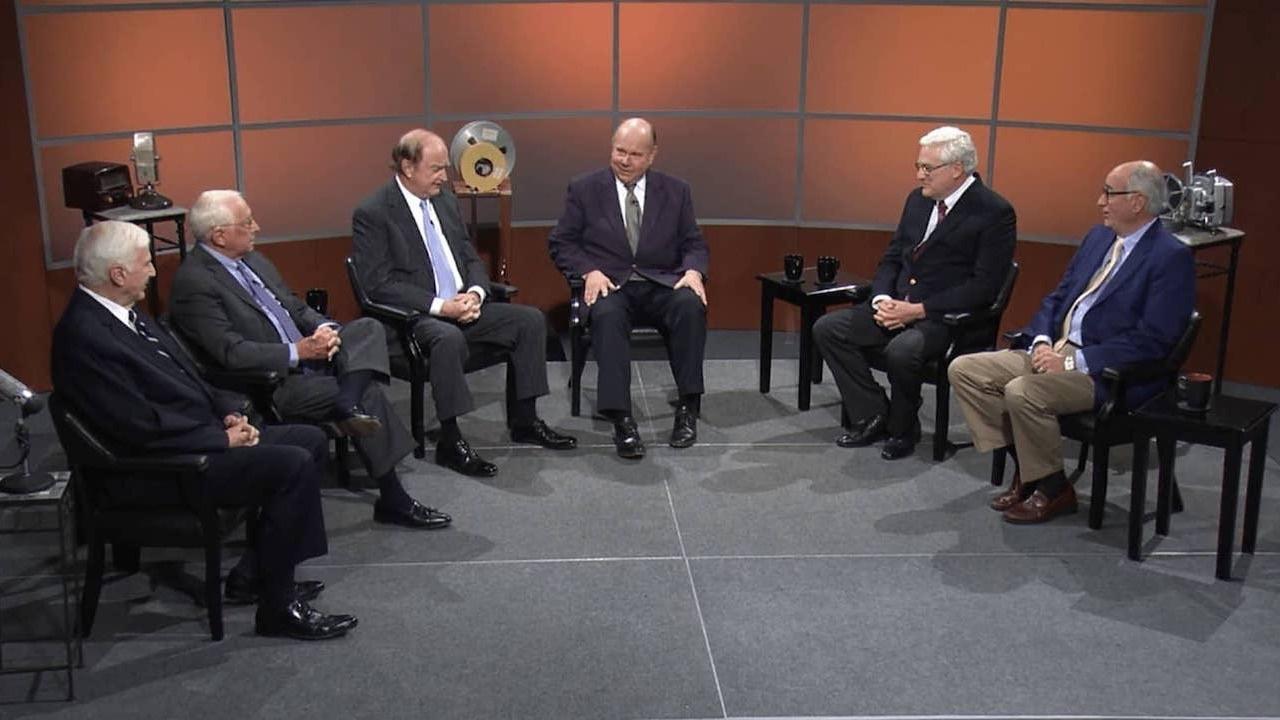 Six men sitting semi-circle on a television set