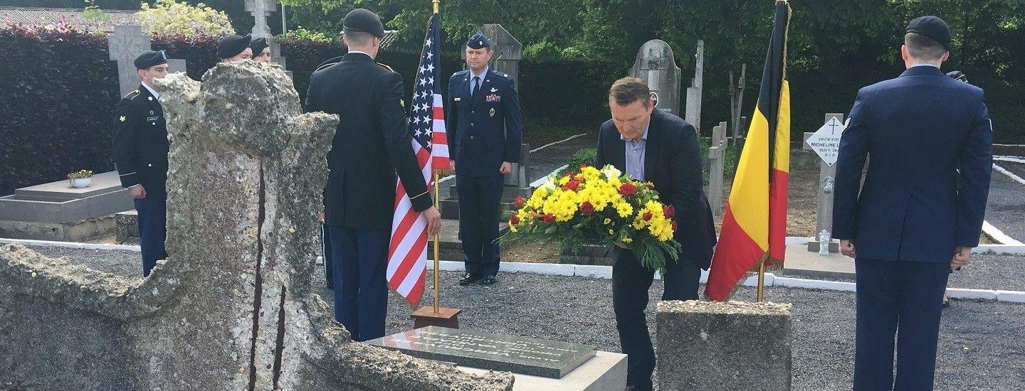 A local mayor lays a wreath at a WWI soldier's grave site.