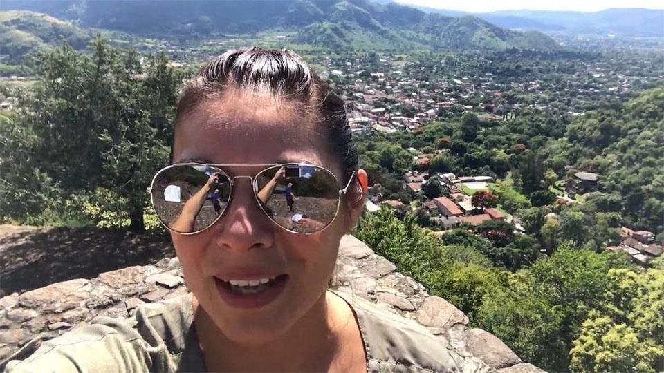 Host Nina Hageness takes a selfie on a mountain with a Mexican village in the background.