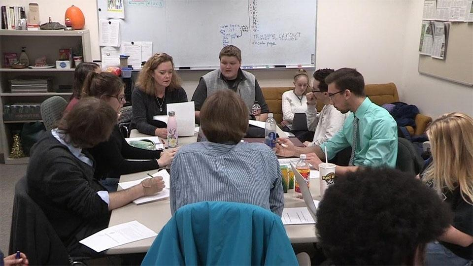 Delta Collegiate writers sit around a table.