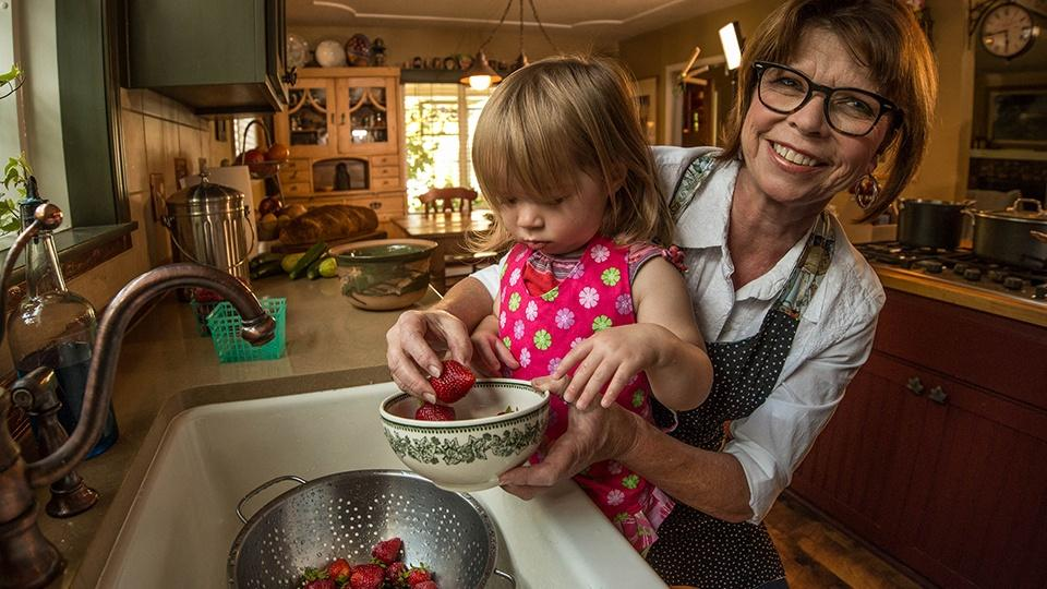 A woman holds her granddaughter up to the kitchen sink and puts washed strawberries into a bowl.