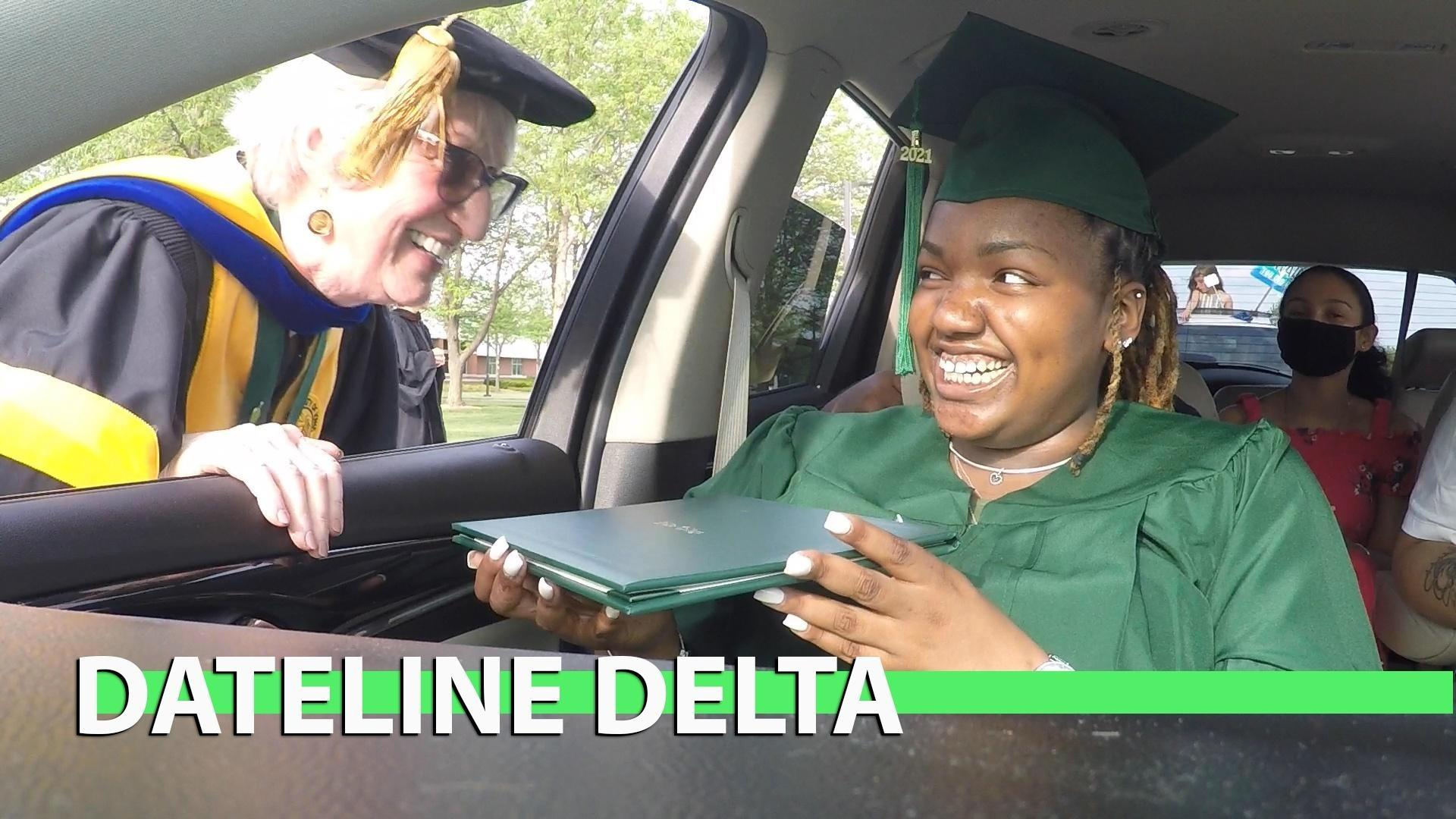 A student in a car receives her diploma from Dr. Goodnow.