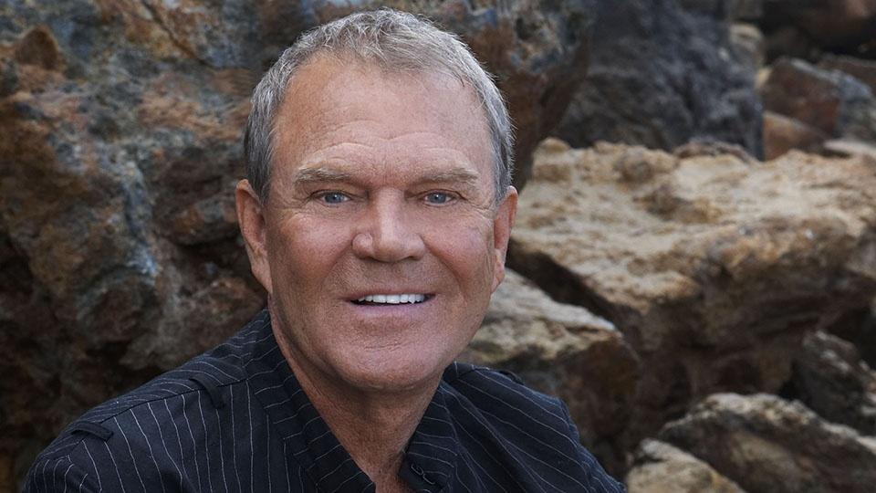Glenn Campbell sitting on rocks.