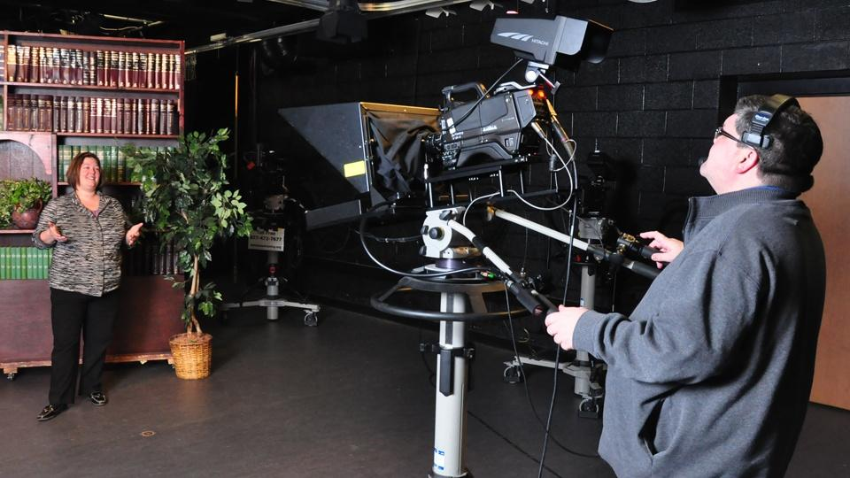 A cameraman films a woman on the Q-TV set.