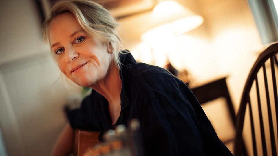 Mary Chapin Carpenter sitting in a chair with an acoustic guitar.