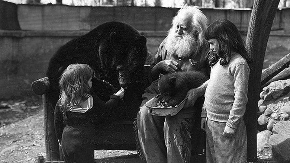 Two young girls feed an adult bear as Spikehorn sits with a bear cub on his lap.