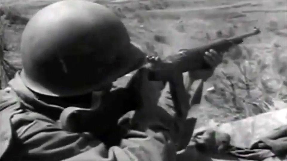 An American soldier in the Korean War firing a rifle.