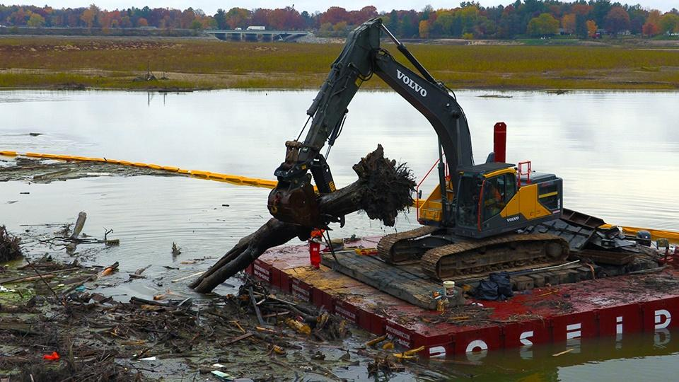 A crane on a raft pulling a dead tree out of the water.