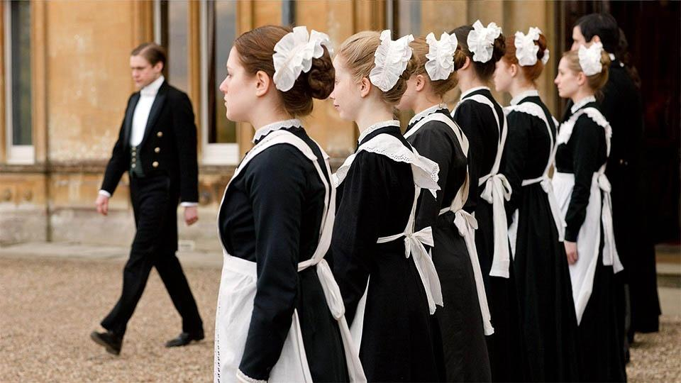 Household servants line up outside of Downton Abbey in a scene from 'Downton Abbey' on 'Masterpiece'.