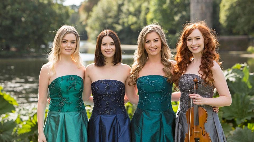The members of Celtic Woman stand on the edge of a river with a forest and a castle in the background.
