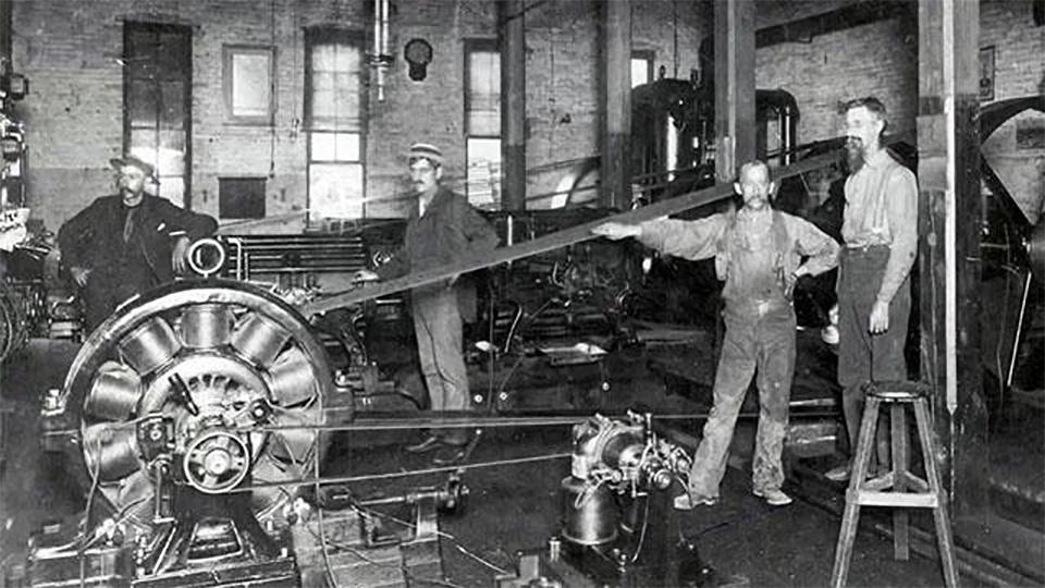 Men work in a 19th-century factory.