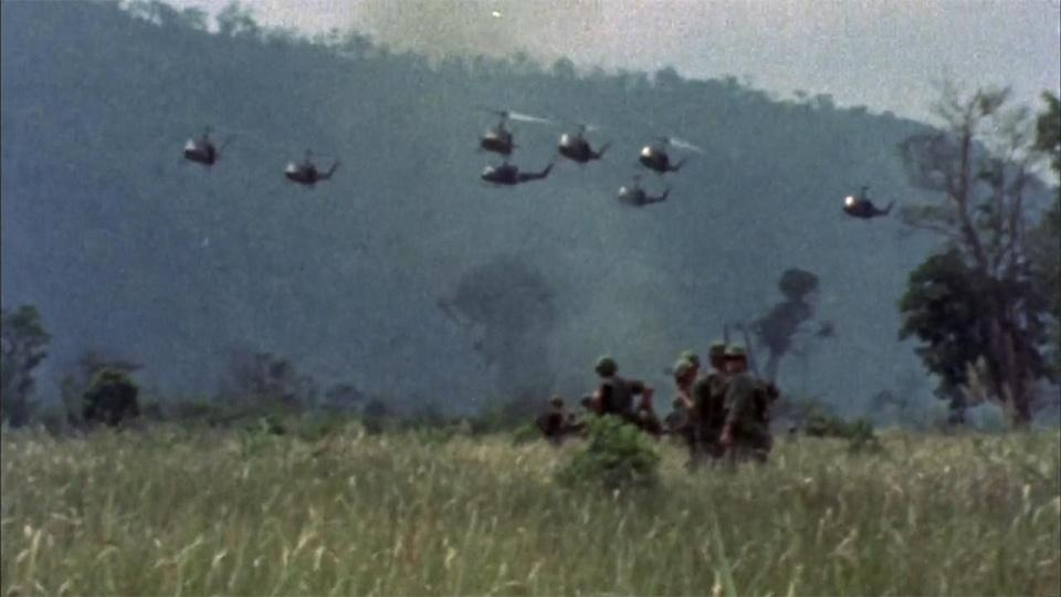 American soldiers walk through a field in Vietnam as helicopters fly across the sky in the distance.