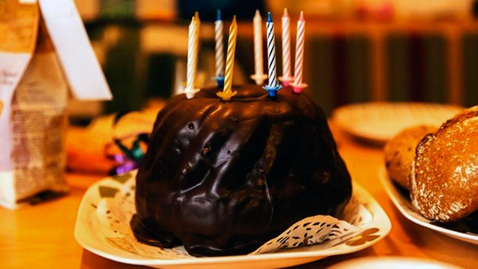 A chocolate birthday cake with candles.