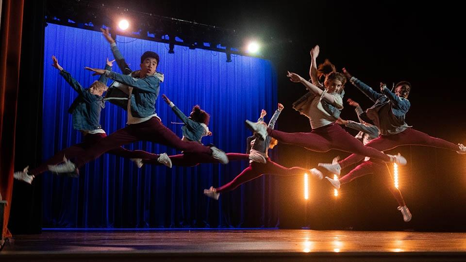 Dancers leaping on a stage.