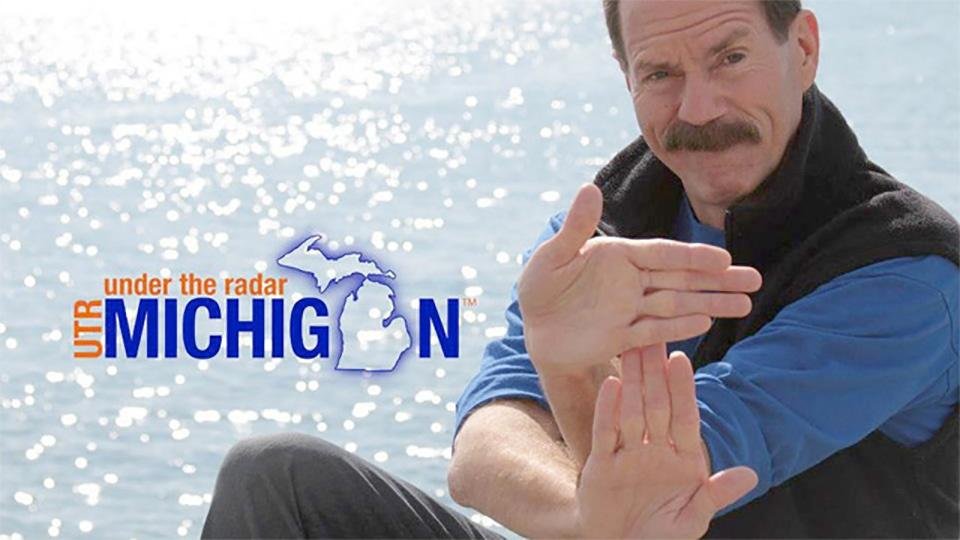 Under the Radar Michigan host Tom Daldin forming a map of Michigan with his hands.