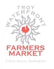 Troy Waterfront Farmers Market logo with Troy Waterfront in gray and all caps above a sun symbol with a red rooster in the middle. The words Farmers Market are below in all caps with the tagline: a four season marketplace below in gray italics.