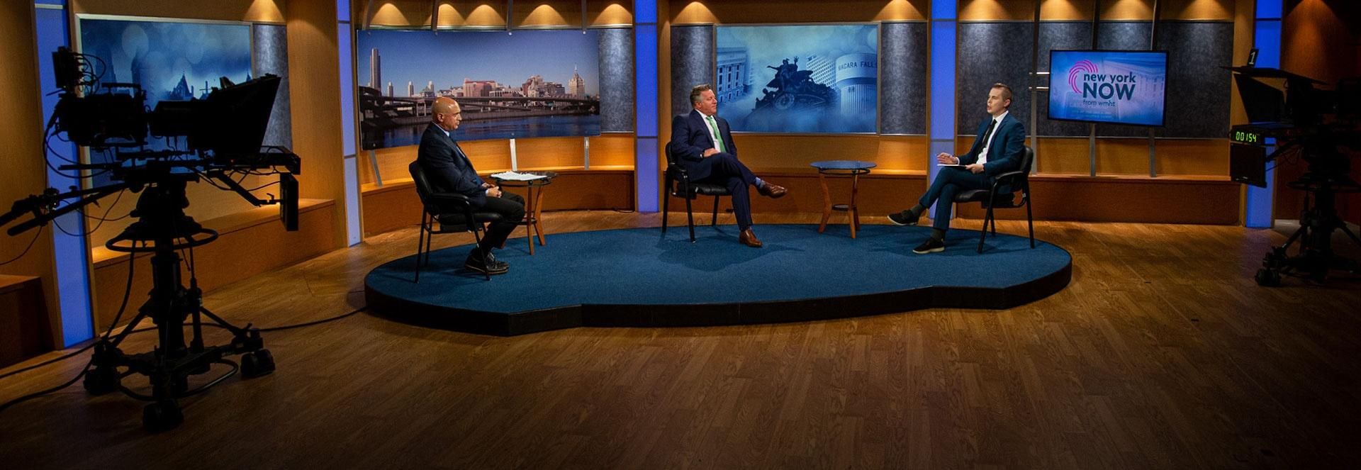 Three individuals are seated in chairs on a platform in a television studio during and interview while practicing social distancing.