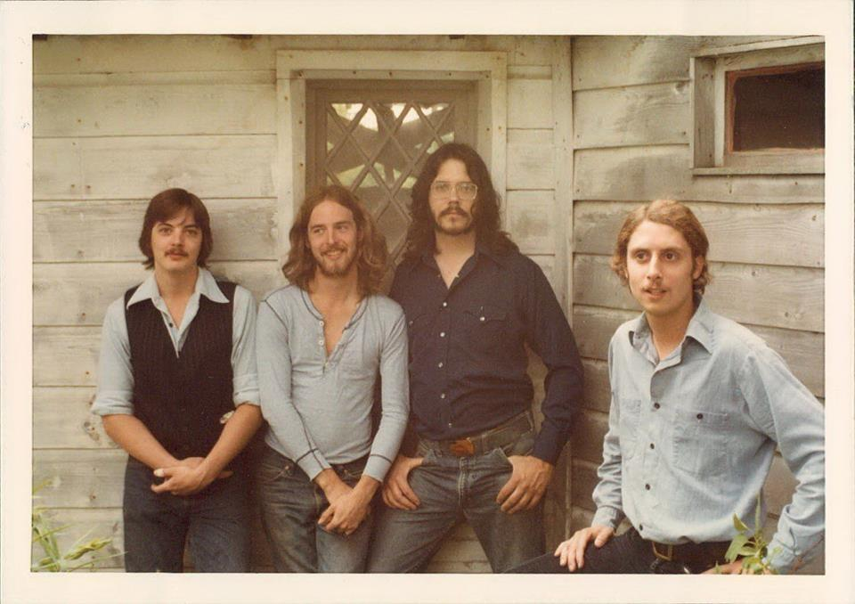 The band Silver Chicken posing in front a house with worn wooden siding.