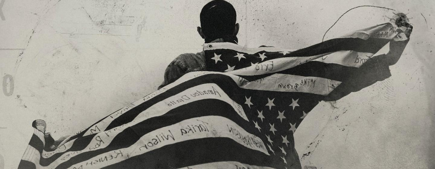 Black and white image of the back of an African American Man holding an American Flag Behind him