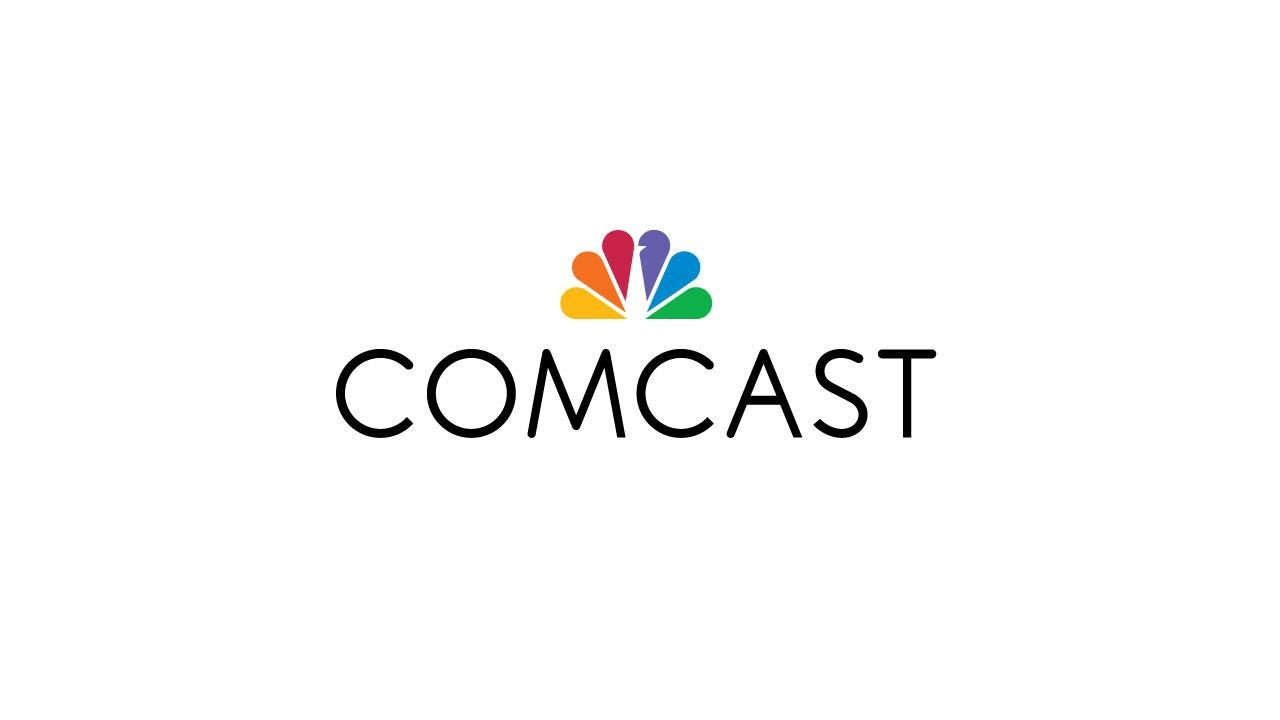 Comcast logo features black sans serif type and the NBC Universal peacock logo.