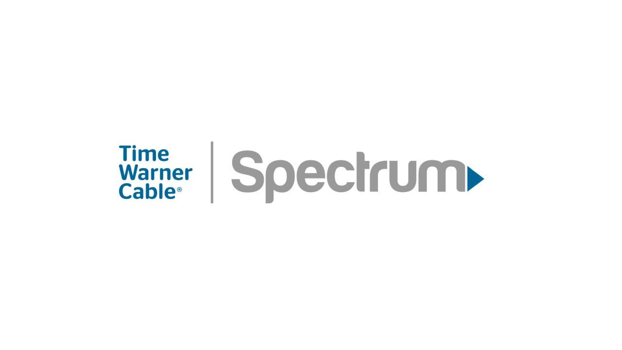 The Time Warner Cable logo in a blue sans serif font on three lines with the Spectrum logo in a gray sand serif font to the right.