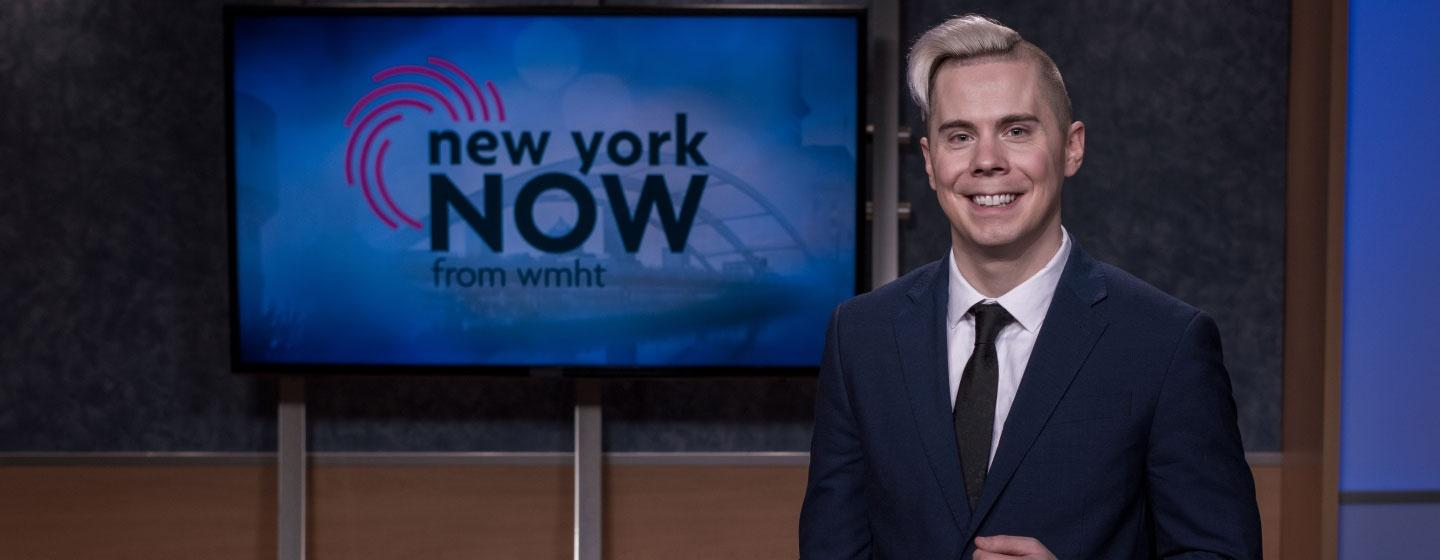 Dan Clark, host and producer of New York NOW, is standing while smiling next to a TV monitor with the New York NOW logo on it. He's wearing a dark blue suit, white collar shirt, and a black necktie.