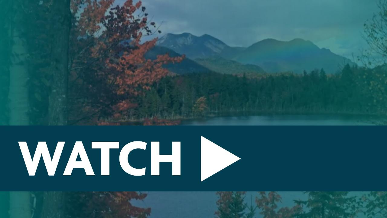 Blue banner with the word WATCH and a triangle play button sits on top of a landscape image with a blue transparency