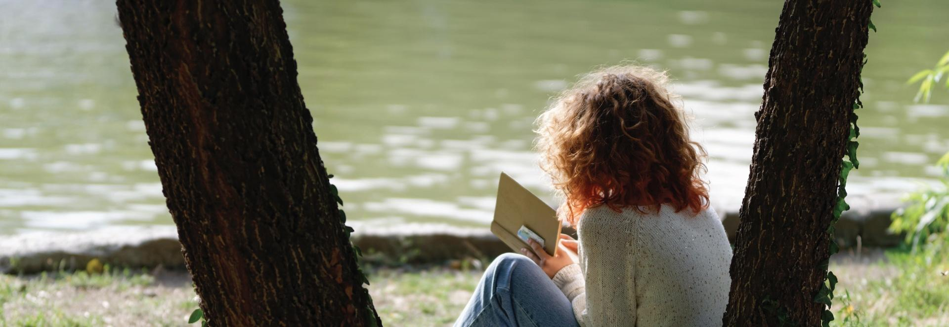 Woman reading a book by a body of water