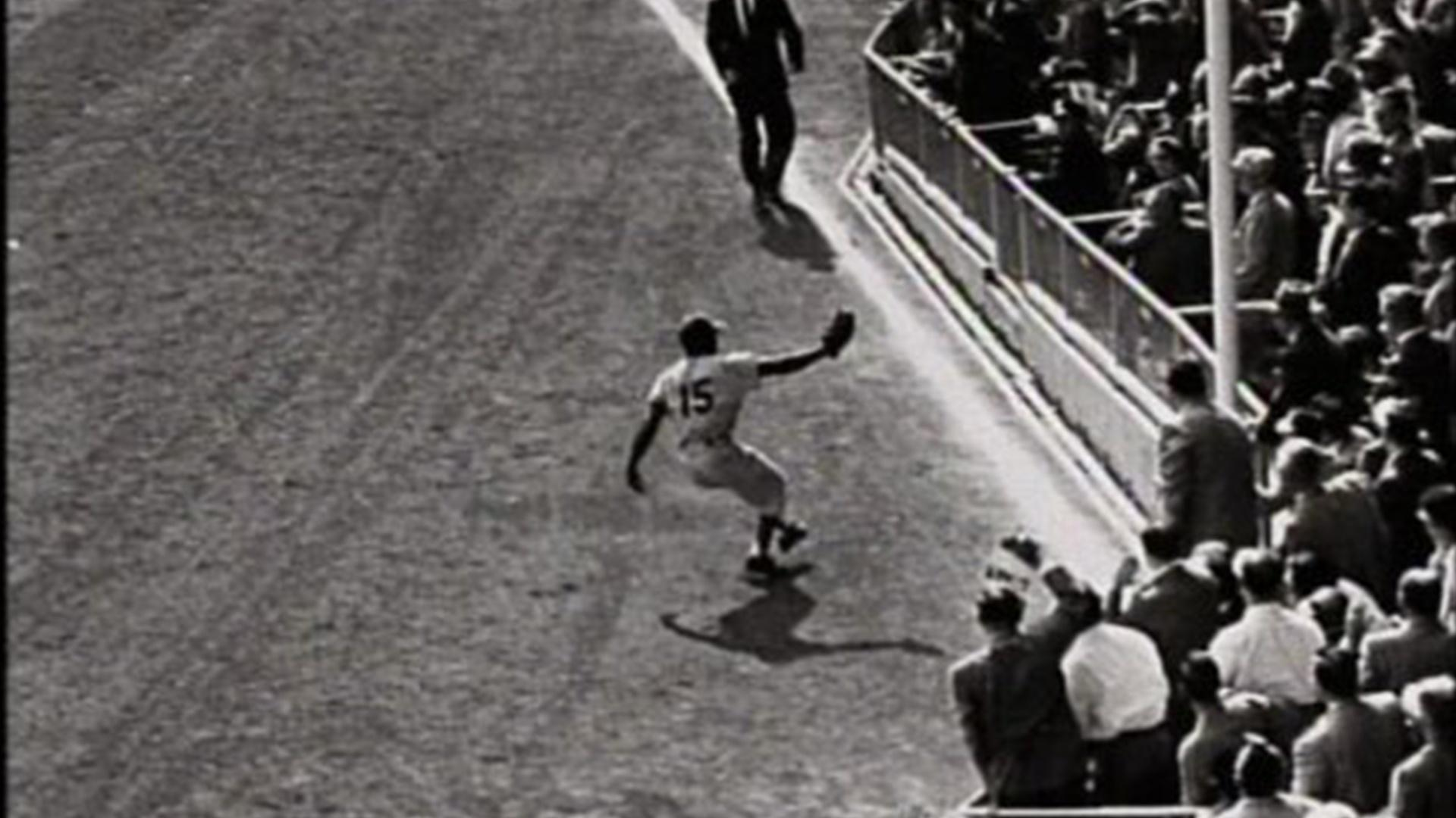 A baseball player on a field reaches out his glove to catch a fly ball.