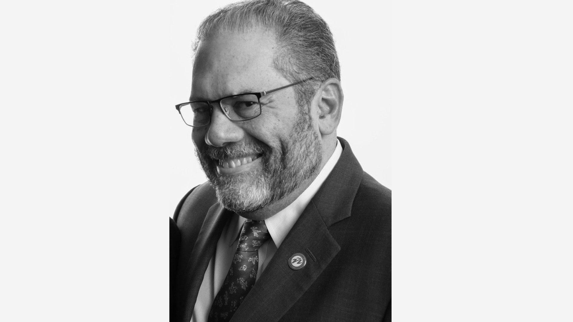 A black and white head shot of Ray Suarez. Ray has a beard and has on glasses while wearing a suit with a collared shirt and necktie.