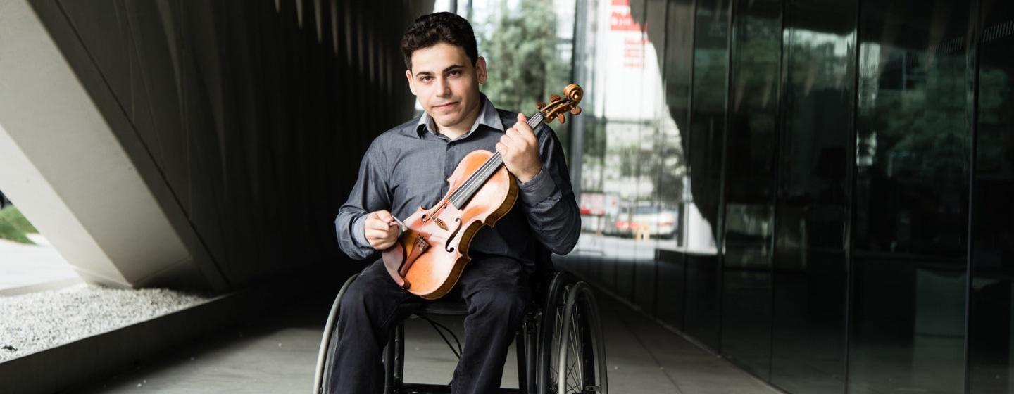 Violinist Niv Ashkenazy sits in a wheelchair while holding violin and a bow.