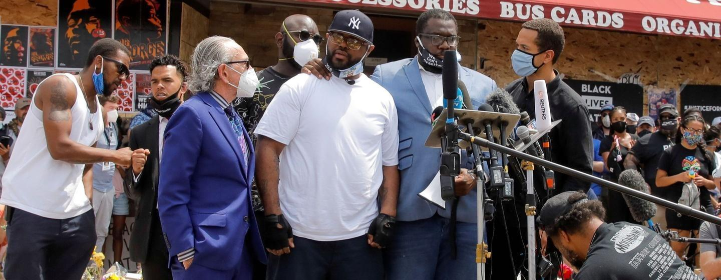 Activists speak at a protest in front of a business.