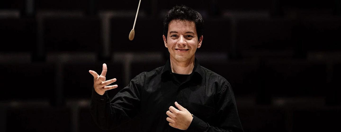 Empire State Youth Orchestra Music Director,wearing all black, stands in the center of the image while twirling a conductor's wand.